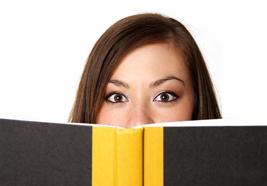 Woman Peering Over Top of Book